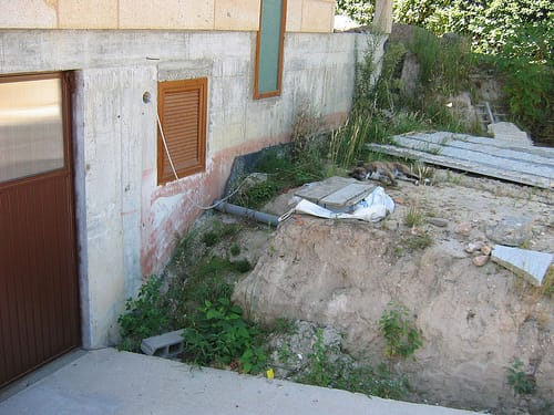 que el primer tramo de escalera sube desde la salida del garaje hasta la explanada pegado a la fachada paralelo a ella donde descansa el boxer